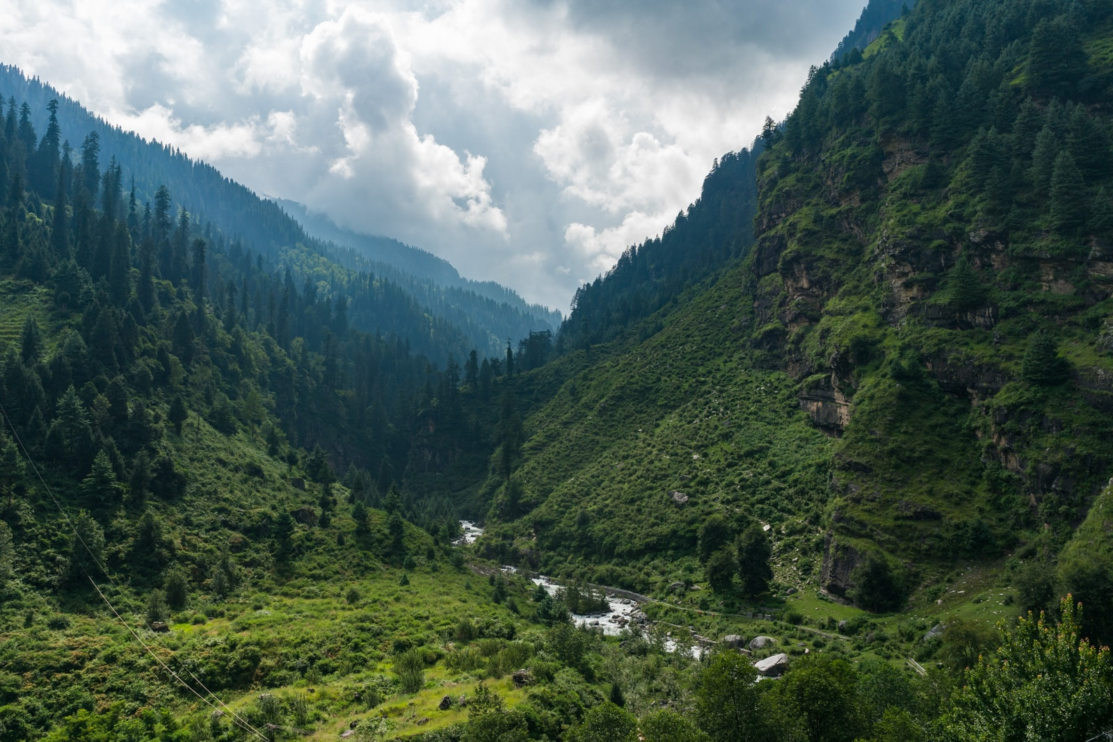 Green forested mountains with a small river running down a valley near Manali in Himachal Pradesh, India