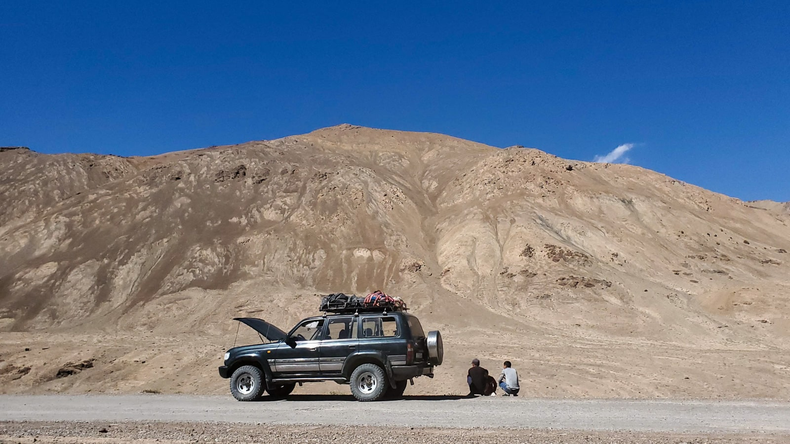 Men sitting by a jeep on the Pamir Highway in Tajikistan