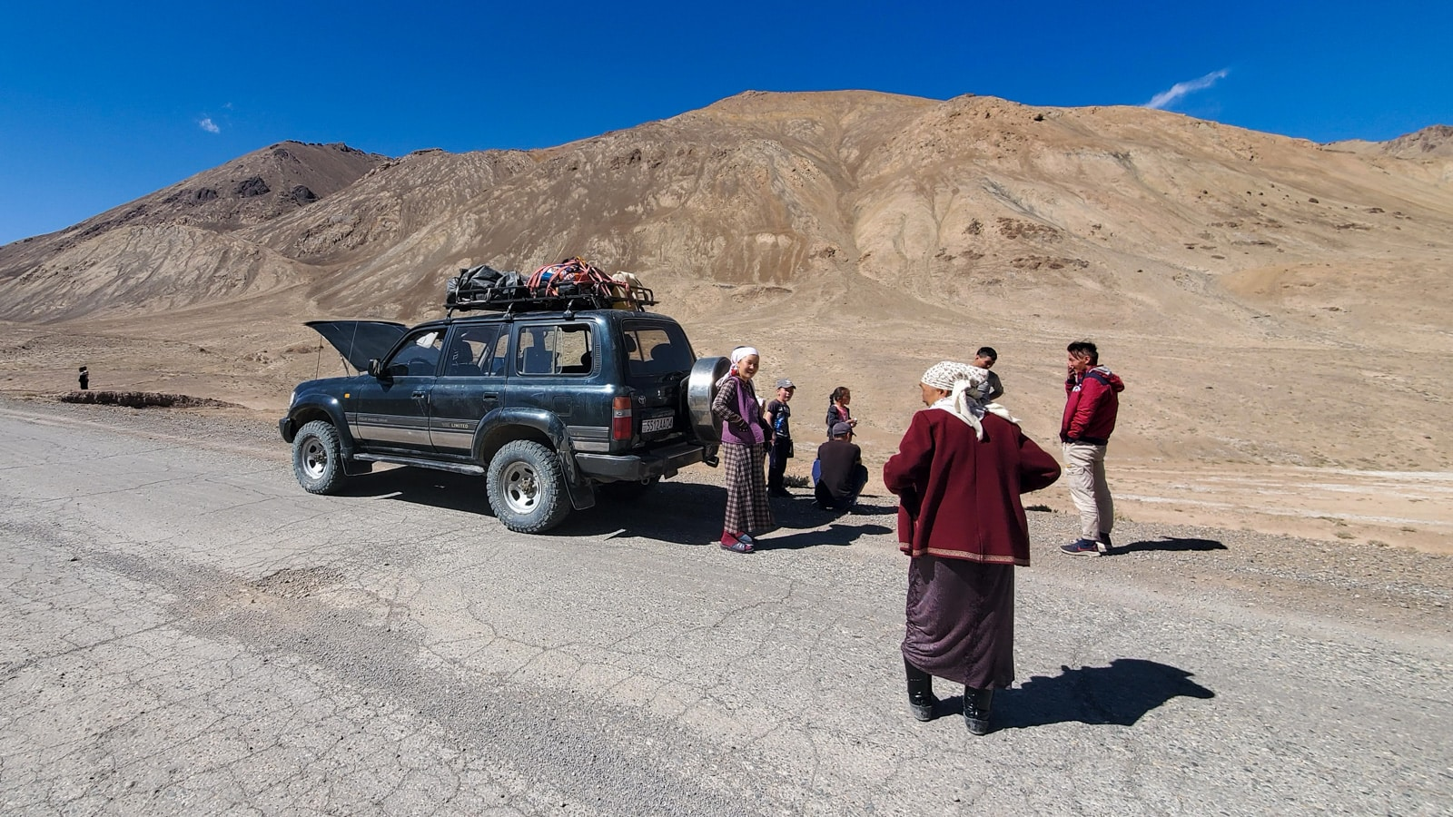 Kyrgyz passengers by a jeep on the Pamir Highway in Tajikistan