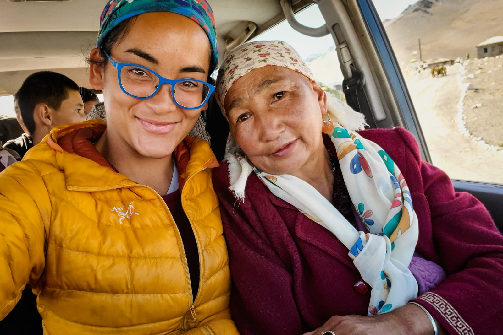 Alex with a smiling older Kyrgyz woman inside a Jeep on the Pamir Highway