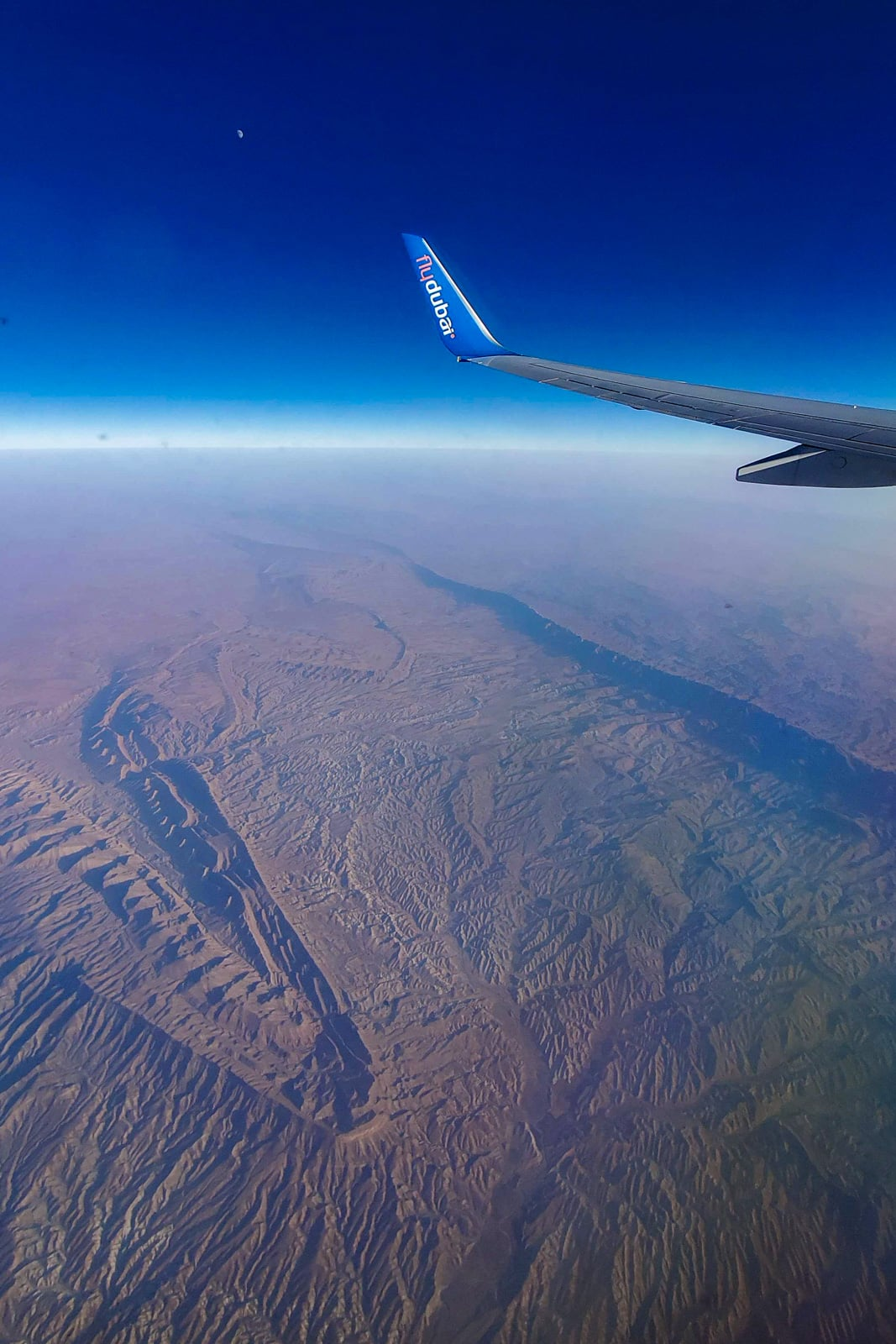 Fly Dubai plane wing flying over desert rock formations