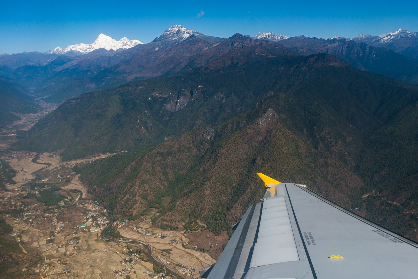 Plane wing flying over Bhutan