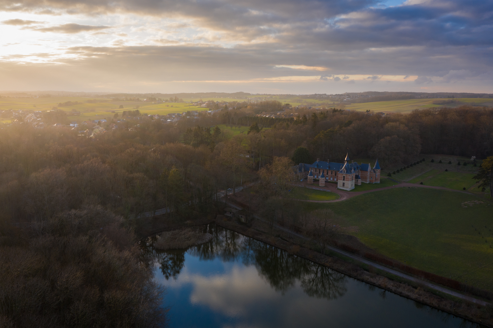 Leefdaal castle at sunrise as clouds reflect in the nearby lake