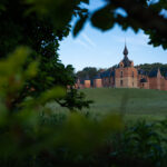 Leefdaal castle in Flemish Brabant, Belgium through a hole in a leafy hedge