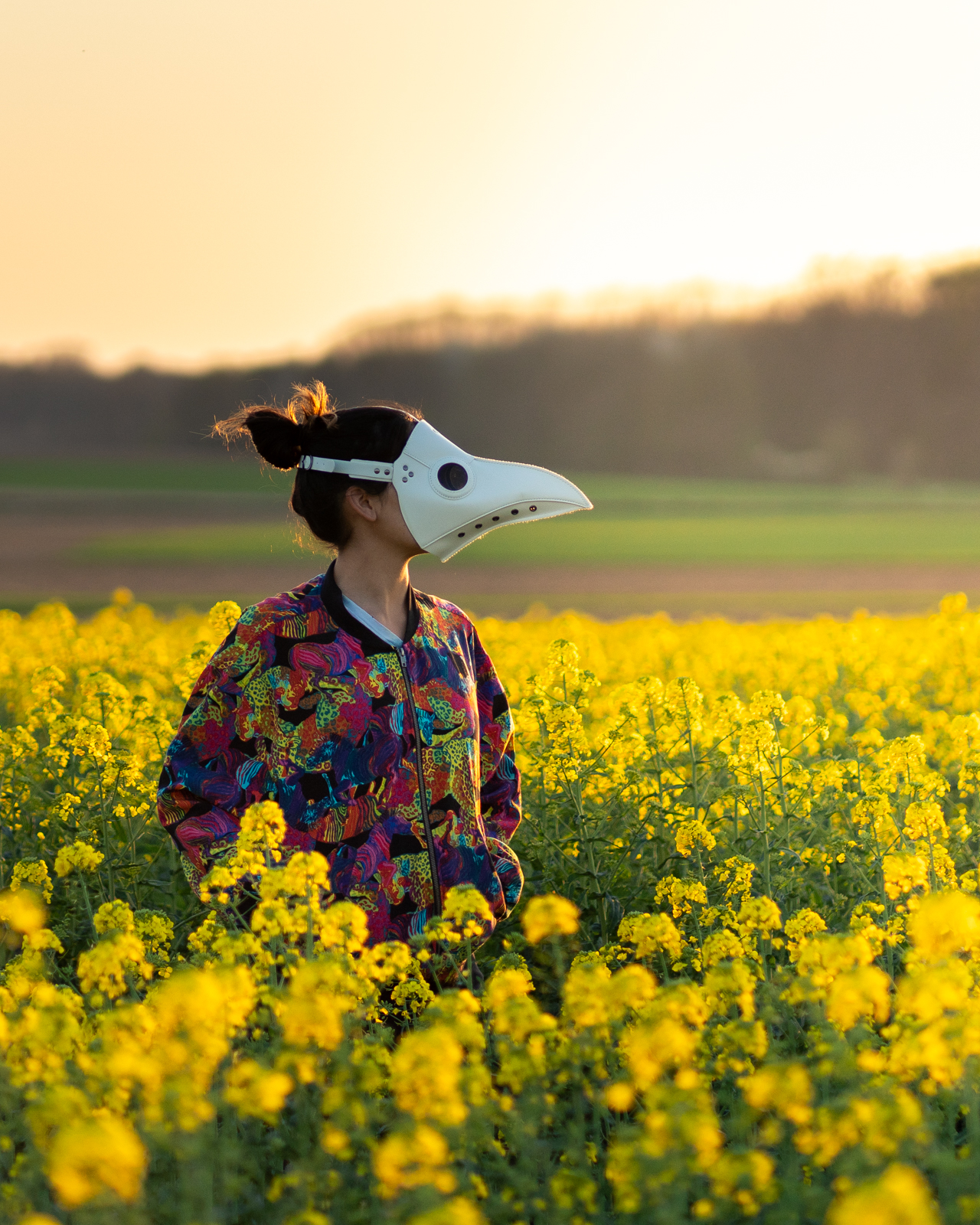 Alex in a white plague doctor mask standing in a field of flowers